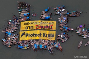 "THAILAND - KRABI, November 9, 2014 : Local fishers gather around a giant banner with a message ""Protect Krabi"" as they take part during a demonstrate against a local coal-fired power plant project at the mangrove area in Krabi's river estuary on November 9, 2014. More than 70 local fishing boats and local fishers are protesting against a local coal-fired power plant project. (Photo by ©Greenpeace)"